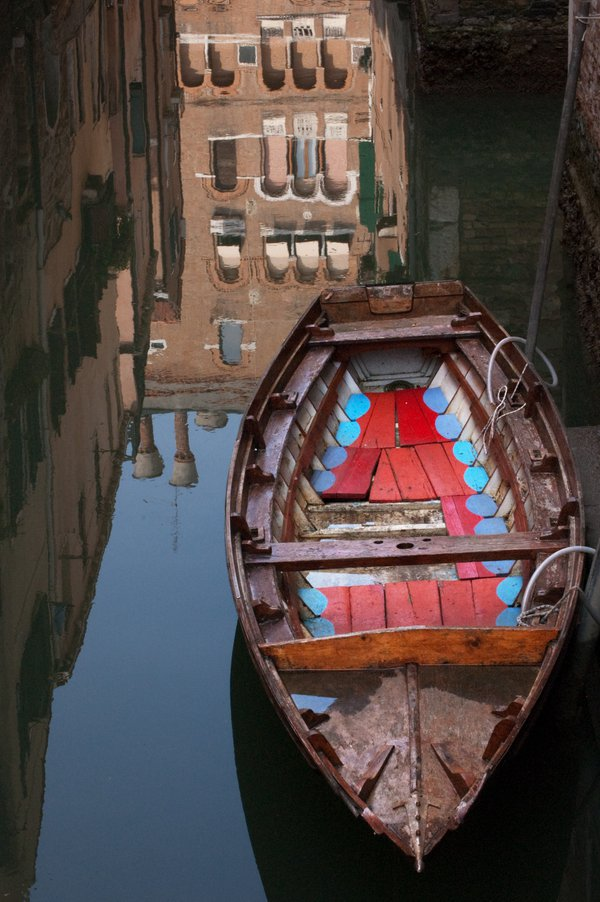 A boat and reflections in the still water of a Venice canal thumbnail