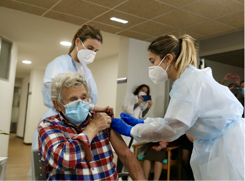 An elderly woman wearing a blue mask received a vaccine from two nurses wearing personal protective equipment