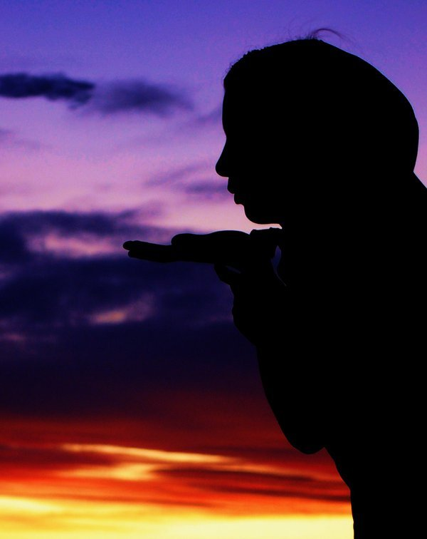 Hutterite girl blowing kisses into the sunset. thumbnail