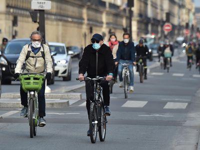 """People in France bike wearing masks down the """"Rue de Rivoli."""""""