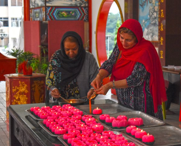 Two ladies burning incense stick for a prayer thumbnail