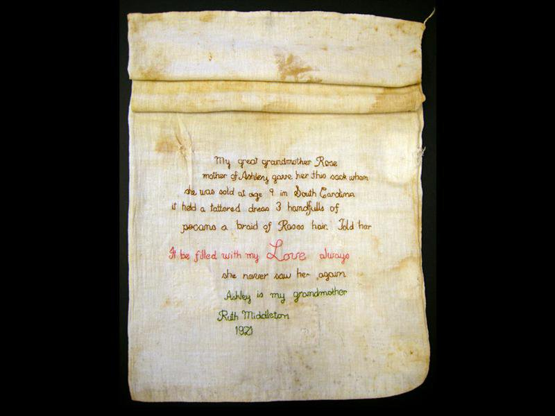 A yellowed, stained sack made from pale white cotton, with its top two thirds roll and its lower segment extended to reveal an embroidered message, stitched in elegant looping script
