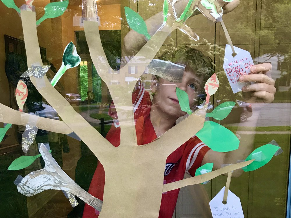 A boy adds a wish for the health of delivery workers during the 2020 pandemic. This  paper wish tree is inspired by artist Yoko Ono's Wish Tree for Washington, on view at the Hirshhorn Museum's Sculpture Garden.