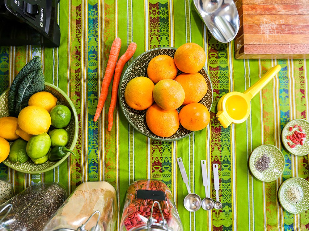 Bowls of citrus fruits including lemons, limes, and oranges, are arranged on a striped, bright green table cloth. Behind the bowls are jars filled with various superfoods including Goji berries.