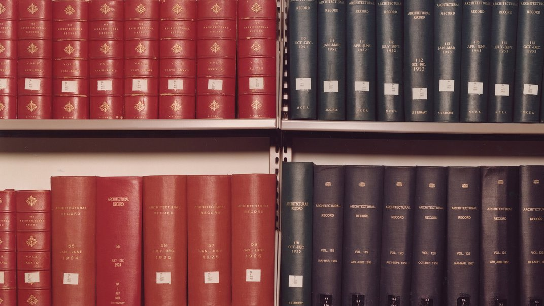 Photo of library book shelves, books bound in red on the left and books bound in navy blue on the right.