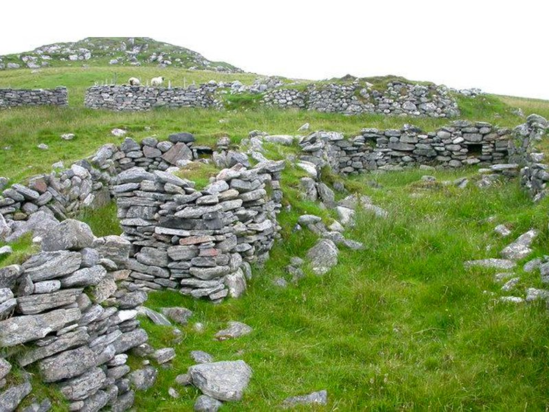 A field of green grass with a glimpse of grey sky behind; in the foreground, low stacked walls of flat rocks form the remains of terraces built into a sloping hill