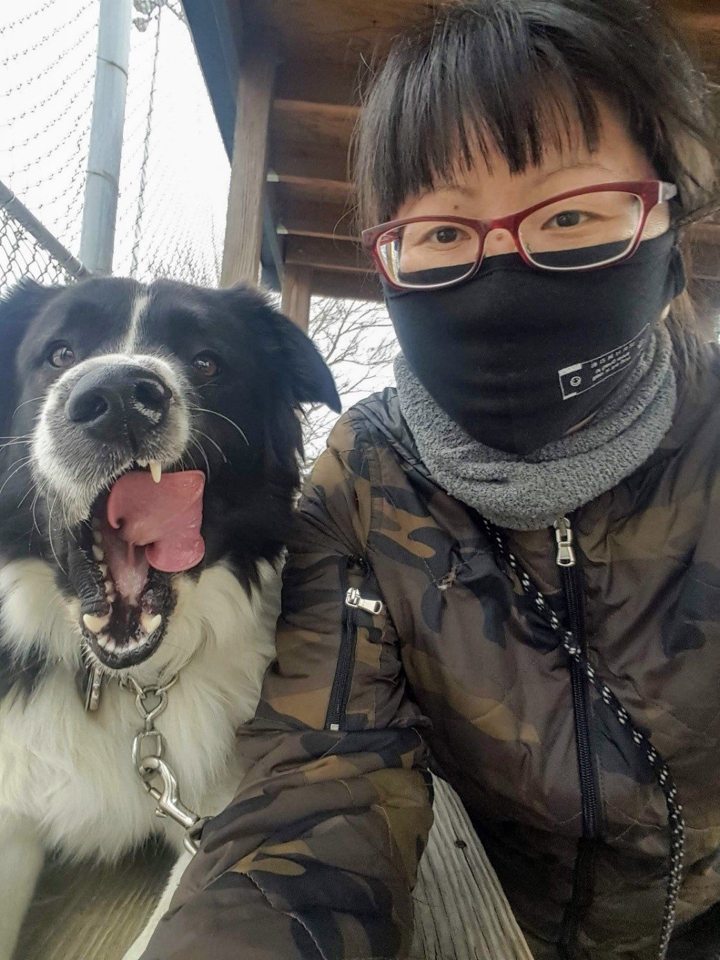 A masked person next to a black and white dog licking its jowls.