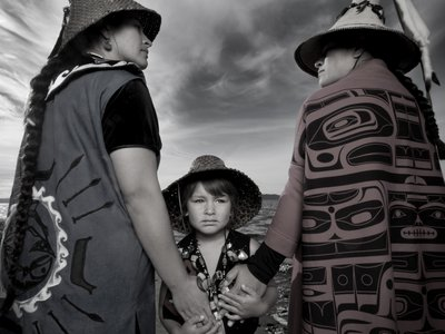 """Darkfeather Ancheta, Eckos Chartraw-Ancheta, and Bibiana Ancheta, Tulalip, Washington. Darkfeather, is pictured with her sister Bibiana and nephew Eckos at the edge of Tulalip Bay. They are wearing traditional regalia prepared for their annual Canoe Journey. Every year, upwards of 100 U.S. tribes, Canadian First Nations and New Zealand canoe families will make """"The Journey"""" by pulling their canoes to a host destination Tribe. Canoe families pull for weeks, and upon landing participate in several days and nights of """"protocol"""", a celebration sharing traditional knowledge, ancestral songs, and sacred dances. Photo by Matika Wilbur for Project 562. Courtesy of the Artist."""