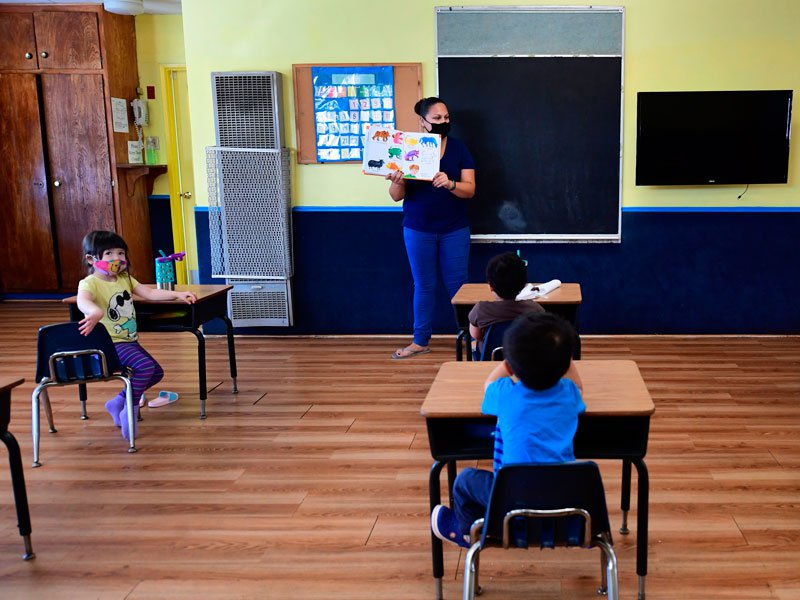 A teacher reads to children in a pre-school class practicing coronavirus precautions