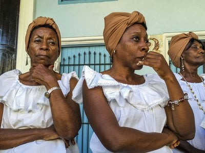 These women in traditional dress are preparing for a street performance in Havana. Despite laws guaranteeing racial equality, black Cubans are generally poorer than whites. And with fewer relatives abroad, they typically receive less in remittances.