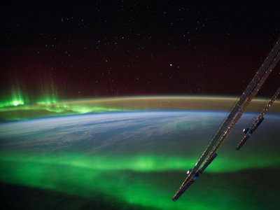 An aurora glows near Australia in a photo taken from the International Space Station. Auroras are products of charged particles from the sun interacting with Earth's magnetic field.